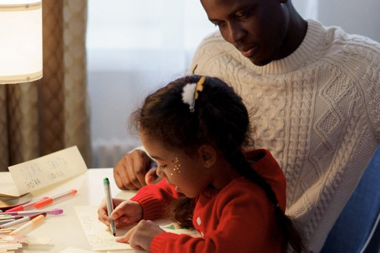 Daughter coloring with her father